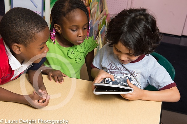 Education preschool 4 year olds boy using tablet computer as classmates look on