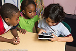 Education preschool 4 year olds boy using tablet computer as classmates look on