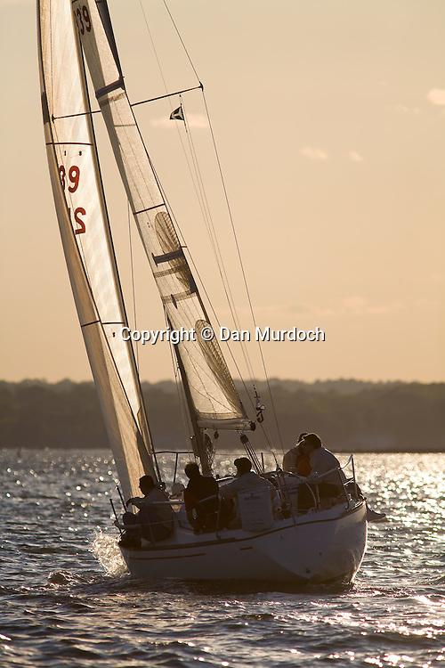 Sailboat heading towards the setting sun