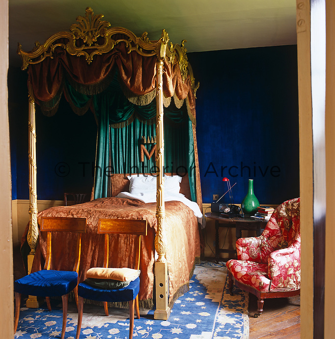 A George III giltwood four-poster bed is covered in an 18th century damask and lined with emerald green silk from India in a room with walls of Prussian blue