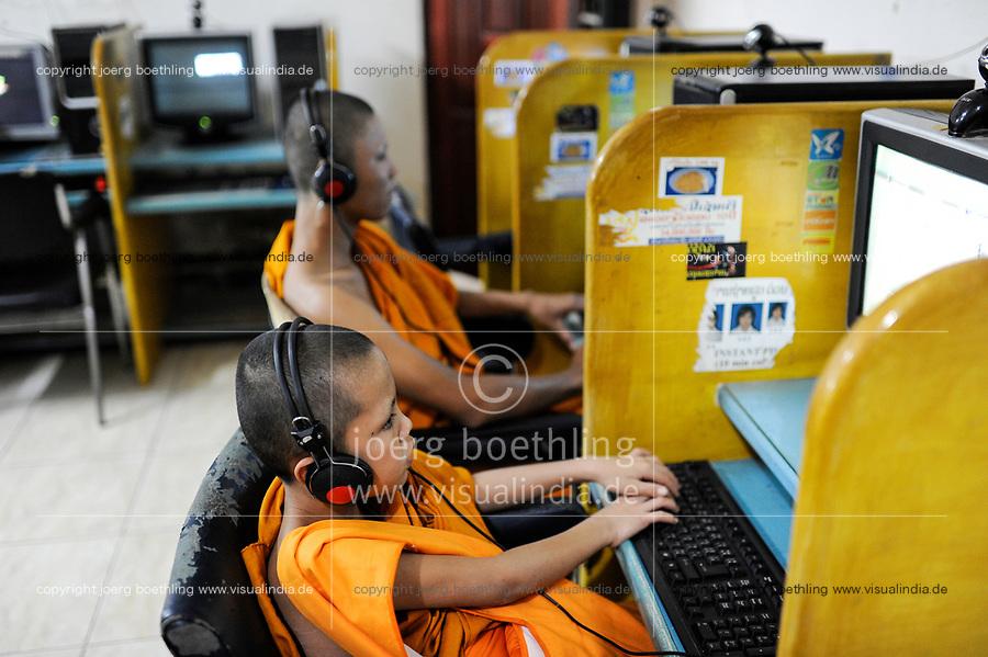 LAO PDR Vientiane, young buddhist monk in Cybercafe playing games at computer / Laos Vientiane , junge budhistische Moenche spielen Computerspiele in einem Internet Cafe