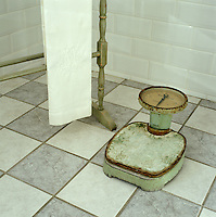 A rusty old-fashioned pair of bathroom scales on the tiled floor