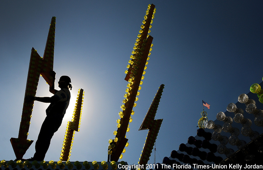 Kelly.Jordan@jacksonville.com--110111--Bob Rogers is silhoutted by the sun as he works to tighten and adjust lights on giant lightning bolts atop the RE-MIX II as crews set-up for the start of the Greater Jacksonville Agricultural Fair at the fairgrounds in Jacksonville, Florida Tuesday November 1, 2011. The ride by Myers International Midways is the fastest ride on the midway. The fair opens Wednesday November 2, 2011 at 5pm.(The Florida Times-Union, Kelly Jordan)