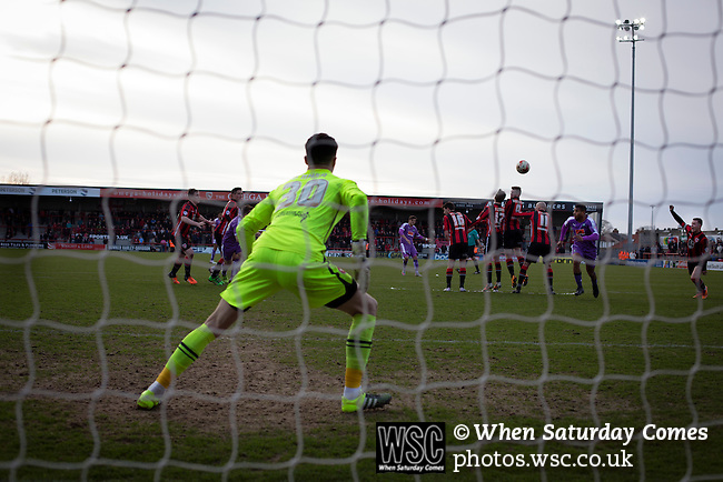 Morecambe 0 Plymouth Argyle 2, 25/03/2016. Globe Arena, League 2. Home keeper Kieran O'Hara prepares to make a save from a free-kick as Morecambe (in red stripes) hosted Plymouth Argyle in a League 2 fixture at the Globe Arena. The stadium was opened in 2010 and replaced Morecambe's traditional home of Christie Park which had been their home since 1921, the year after their foundation. Plymouth won this fixture by 2-0 watched by 2,081 spectators, in a game delayed by 30 minutes due to traffic congestion affecting travelling Argyle fans.  Photo by Colin McPherson.