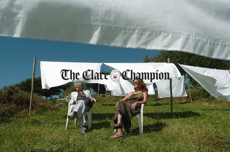 Bellhar artist Maria Kerin, right, with her friend Beth O Connell at the Sweet Bellharbour Art Installation, which runs in a triangular field,  ajacent to Corcomroe Abbey and consists of forty nine white bed sheets, with silver writing on each, naming people who have passed away in the locality, during the artist's lifetime. Photograph by John Kelly.
