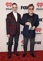 """HOLLYWOOD, CA - MAY 27: Elton John and David Furnish with the award for iHeartRadio Icon at the 2021 """"iHeartRadio Music Awards"""" airing live from The Dolby Theatre in Los Angeles, Thursday, May 27 (8:00-10:00 PM ET live / PT tape-delayed) on FOX. CR: Scott Kirkland/FOX/PictureGroup © 2021 FOX MEDIA, LLC. (Photo by Scott Kirkland/FOX/PictureGroup)"""