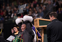 Eva Gregg, B.S.W. Social Work, holds up her degree during UAA's 2019 Spring Commencement at the Alaska Airlines Center.