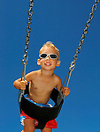 Boy on swing with sunglasses