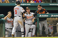 Baltimore Orioles manager Buck Showalter greets Nate McClouth #9 after his home run in the dugout during the Major League Baseball game against the Texas Rangers on August 21st, 2012 at the Rangers Ballpark in Arlington, Texas. The Orioles defeated the Rangers 5-3. (Andrew Woolley/Four Seam Images)..