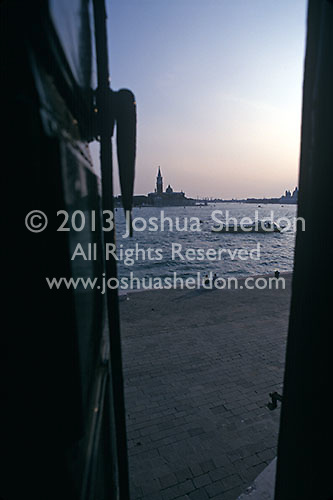 View out shuttered window of a Venice canal and the island of San Giorgio and San Giorgio Maggiore church<br />