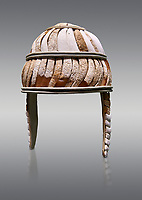 Minoan boar's tusk helmet with cheek guards,1450-1300 BC, Heraklion Archaeological Museum, grey background<br /> <br /> This restored boars tusk helmet was described in Homers Iliad being worn by Cretan hero Meriones. It bis believed that the helmet was ceremonial depicting the rank of an officer, grey background