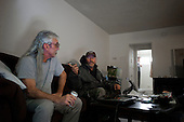 Los Angeles, California<br /> February 1, 2014<br /> <br /> Former homeless Navy veteran 52 year old Raymond McGinnis (center) with his veteran, drinking buddy and former homeless friend Ray (left). Both had been homeless for many years. McGinnis served from 1977 to 1983 and was working as a landscaper when he was hit by a car and permanently injured his leg and subsequently lost his job. He has been in his HUD VASH house for 18 months.