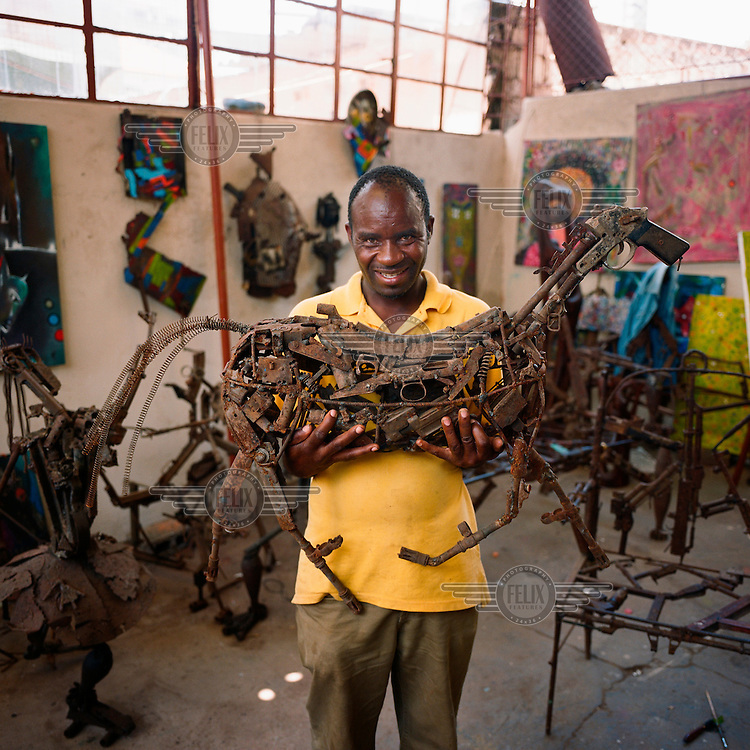 Kester shows one of his sculptures at his shared studio in Maputo. Kester is part of the collective Nucleo de Arte, which for the past few years has been involved in the project Arms into Art, a unique concept that looks to take decommissioned weapons and turn them into works of art.