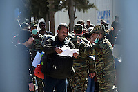 Pictured: A man is given paperwork by a soldier at the refugee camp Tuesday 23 February 2016<br /> Re: Migrants at a refugee camp in the Schisto area of Athens, Greece.