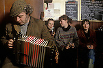 Man farmer playing a melodeon in village pub The Kings Head, Low House, Laxfield Suffolk, UK. 1980s