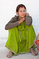 Bodhnath, Nepal.   Visitor at the Buddhist Stupa of Bodhnath.  She wears rings on her toes, an ankle bracelet, and a bindi and tikka on her forehead, with remnants of henna decorations on her wrist and hands.