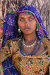 Rajasthani woman, Pushkar Fair, Rajasthan, India<br /> Standing in the shade of a tree, this woman is striking not only because of the color of her dress but also the color of her eyes.<br /> Canon EOS-1Ds, EF70-200mm f/2.8 lens,<br /> f/13 for 1/30 second, ISO 200
