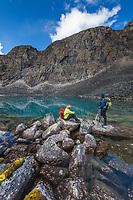 Day hikers gaze at the crystal clear blue water in a mountain lake in the Arrigetch Peaks, Gates of the Arctic National Park, Alaska.
