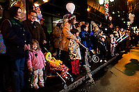 Families of parents and children watch a downtown parade during First Night Charlotte 2010. The family-friendly public event (no alcohol allowed) is an annual cultural New Year's Eve celebration held in downtown / uptown / Charlotte center city. Charlotte First Night - An Imagination Celebration brought together artists, musicians, dancers and more from across the country. The New Year's event is organized by Charlotte Center City Partners, which facilitates and promotes the economic and cultural development of this North Carolina urban core.