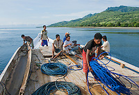 Passengers and crew on the deck of a small boat leaving the dock at Beloi, Atauro Island, bound for Dili, Timor-Leste (East Timor)