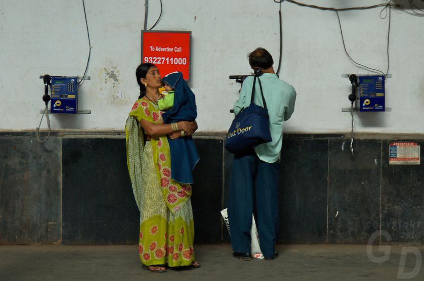 A couple makeing a call at theMumbai Railway station, Mumbai India