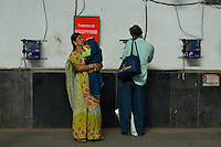A couple makeing a call at theMumbai Railway station, Mumbai India