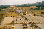 Local farmer Mike Stephens, who farm has been cut in half herding his sheep across the M40 motorway thats under construction 1980s Banbury Oxfordshire UK.