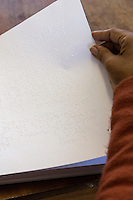 South Africa, Cape Town.  Editor Examining Braille Workbooks Printed for Students.  Athlone School for the Blind.