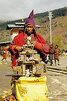 Bhutan, Thimpu.  Mendicant Buddhist monk collecting in the street.