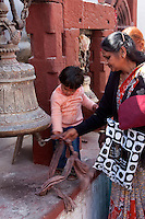 Bodhnath, Nepal.  A Mother Teaching her Child to Ring a Bell to Drive Away Evil Spirits.