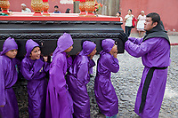 Antigua, Guatemala.  An Adult Cucurucho Prepares Adolescent Boys for a Turn at a Street Corner as they Carry a Float (Anda) in a Religious Procession during Holy Week, La Semana Santa.
