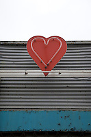 A red heart-shaped neon light on the exterior of a cafe