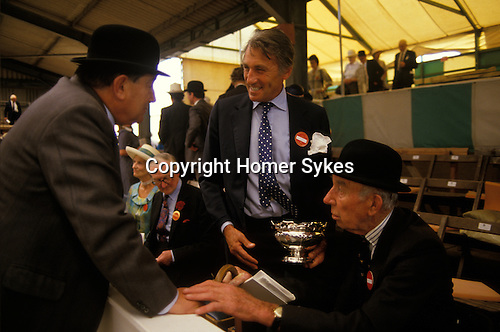 Peterborough, Cambridgeshire. 1980's<br /> David Somerset the 11th Duke of Beaufort, with two bowler hatted officials, discuss the quality of the hounds, before presenting a silver Rose Bowl, as the first prize at the Peterborough Hound Show. 1980s UK