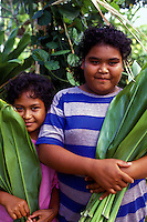 Two young girls carrying ti leaves they gathered in Yap, Micronesia.