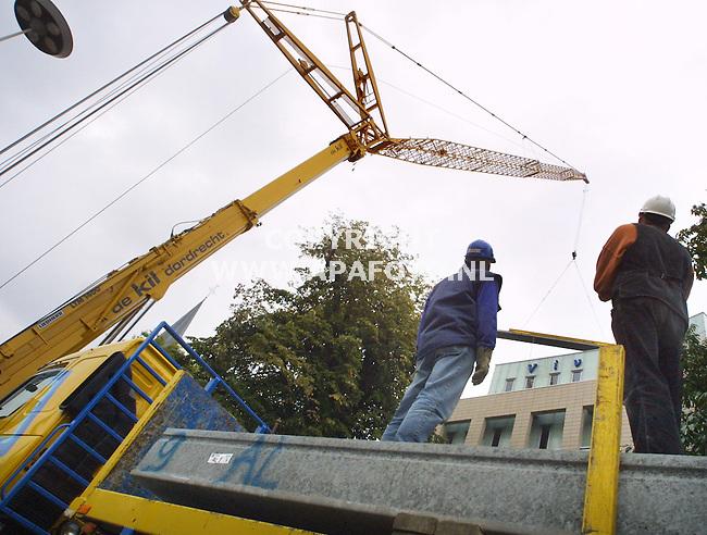 Arnhem, 041001<br />Twee werknemers van de Kil uit Dordrecht kijken toe hoe beton over het Vivare gebouw wordt getild door een '400 tonner' Liebherr met een mast van  totaal 85 meter lengte.   Het beton wordt gebruikt voor een parkeergarage achter het Vivare gebouw. Deze lange kraan valt erg op langs de Steenstraat  in het centrum van Arnhem.<br />Foto: Sjef Prins / APA Foto