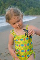 Young girl handles a Leatherback Sea Turtle hatchling on beach. Dermochelys coriacea. Matura Beach, Trinidad.