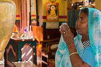Nepal, Kathmandu, Swayambhunath.  Buddhist Woman Praying in front of a Buddha Shrine.