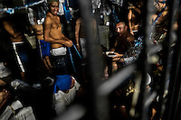 """Members of the Mara Salvatrucha gang (MS-13) eat lunch in an overcrowded cell at the detention center in San Salvador, El Salvador, 20 February 2014. Although the country's two major gangs reached a truce in 2012, the police holding cells currently house more than 3000 inmates, five times more than the official built capacity. Partly because the ordinary Mara gang members did not break with their criminal activities (extortion, street-level distribution of drugs, etc.), partly because Salvadorean police still applies controversial anti-gang law which allows to detain almost anyone for """"suspicion of gang membership"""". Accused young men are held in police detention centers where up to 25 inmates may share a cell of five-by-five metres. Here, in the dark overcrowded cages, under harsh and life-threatening conditions, suspected gang members wait long months, sometimes years, for trial or for to be transported to a regular prison."""