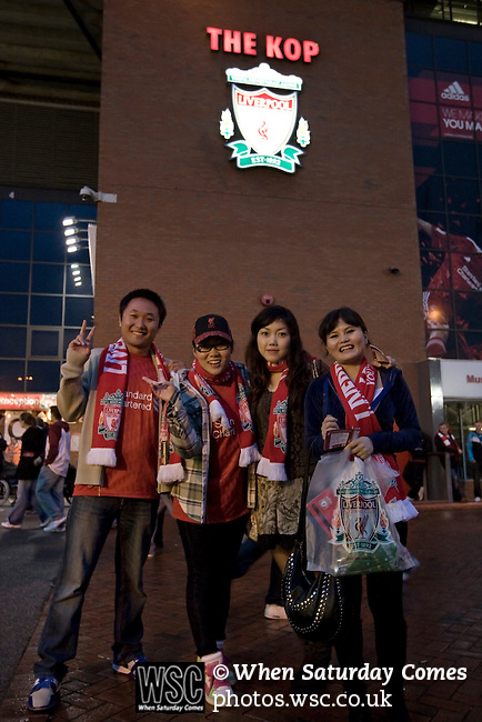Liverpool 2 Northampton Town 2, 22/09/2010. Anfield, League Cup third round. Three Liverpool supporters from China posing for a photograph outside the Kop at Anfield, before their team's Carling Cup third round tie at home to Northampton Town. The visitors from English League 2 defeated Premier League Liverpool on penalty kicks after a 2-2 draw after extra time in one of the biggest shock results in either clubs histories. Photo by Colin McPherson.
