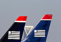 US Airways jets sit at the gates, with the Charlotte skyline in the background, at Charlotte-Douglas International Airport in Charlotte, North Carolina. Charlotte-based photographer has other images of transportation, airplanes on runways (and taking off and landing) and interior/exterior airport images of Charlotte-Douglas Intl Airport in portfolio.