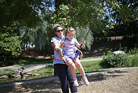 Jenna Martin of Bella Vista (from left) swings Bryn Martin, 5, Sunday, September 5, 2021 at Horsebarn Trailhead Park in Rogers. Check out nwaonline.com/210906Daily/ for today's photo gallery. <br /> (NWA Democrat-Gazette/Charlie Kaijo)