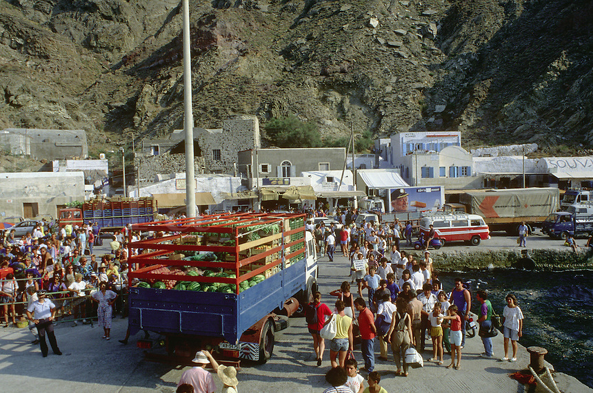 Truckloads of watermelons and vegetables debark at the ferry port on the island of Santorini as tourists await their turn to board.