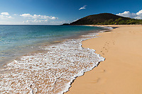 A clear and sunny day at Makena Beach, Maui, with people enjoying the distant side of the beach.