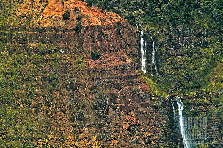 """A comparatively small tourist helicopter on the left flies close to Waipo'o Falls in Kaua'i's Waimea Canyon, which some call """"the Grand Canyon of the Pacific."""""""