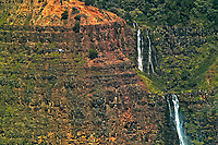"A comparatively small tourist helicopter on the left flies close to Waipo'o Falls in Kaua'i's Waimea Canyon, which some call ""the Grand Canyon of the Pacific."""