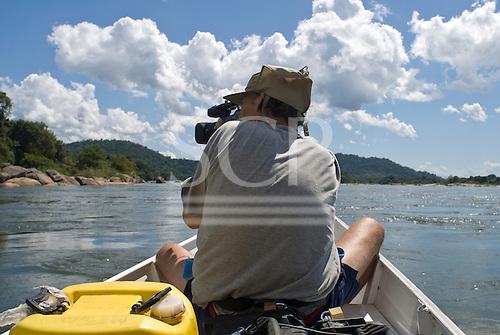 Pará State, Brazil. Xingu River. Patrick Cunningham using a video camera.