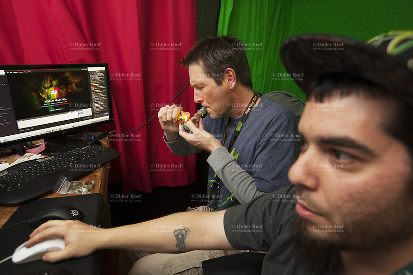 USA. Colorado state. Denver. Jesse Toks (R )works during the day at Medicine Man and plays internet video games at home in the evenings and weekends. Pete Williams (L), owner of Medicine Man, lights a marijuana pipe while watching the online gamer playing. Medicine Man began nearly six years ago as a small medical marijuana operation and has since grown to be the largest single marijuana dispensary, both recreational and medical, in the state of Colorado and has aspirations of becoming a national brand if pot legalization continues its march. Cannabis, commonly known as marijuana, is a preparation of the Cannabis plant intended for use as a psychoactive drug and as medicine. Pharmacologically, the principal psychoactive constituent of cannabis is tetrahydrocannabinol (THC); it is one of 483 known compounds in the plant, including at least 84 other cannabinoids, such as cannabidiol (CBD), cannabinol (CBN), tetrahydrocannabivarin (THCV), and cannabigerol (CBG). 18.12.2014 © 2014 Didier Ruef
