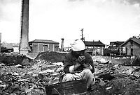 An aged Korean woman pauses in her search for salvageable materials among the ruins of Seoul, Korea.  November 1, 1950.  Capt. C. W. Huff. (Army)<br /> NARA FILE #:  111-SC-351700<br /> WAR & CONFLICT BOOK #:  1504