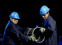 Model released  File Photo<br /> <br /> Two workers assemble plastic pipes<br /> <br /> Mandatory Credit: Photo by Pierre Roussel- Images Distribution. (©) Copyright 2004 by Pierre Roussel <br /> <br /> NOTE : scan from 2 1/4 slide