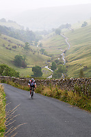 UK, England.  Bicycle Rider Climbing Steep Hill on an Autumn Day in the Yorkshire Dales.